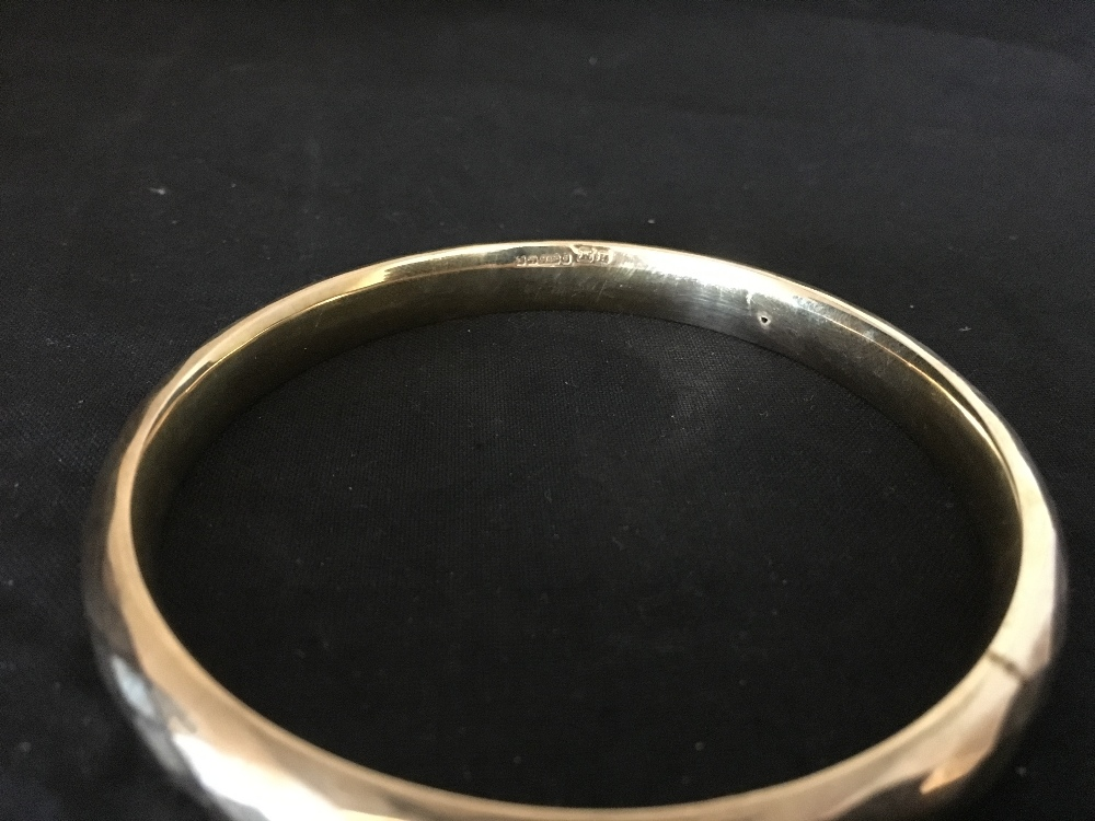Lot 57 - A 9ct gold bangle.