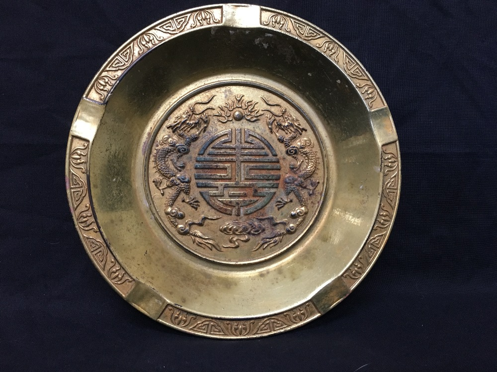 Lot 15 - A heavy yellow metal dish with two Chinese Imperial dragons to the centre.