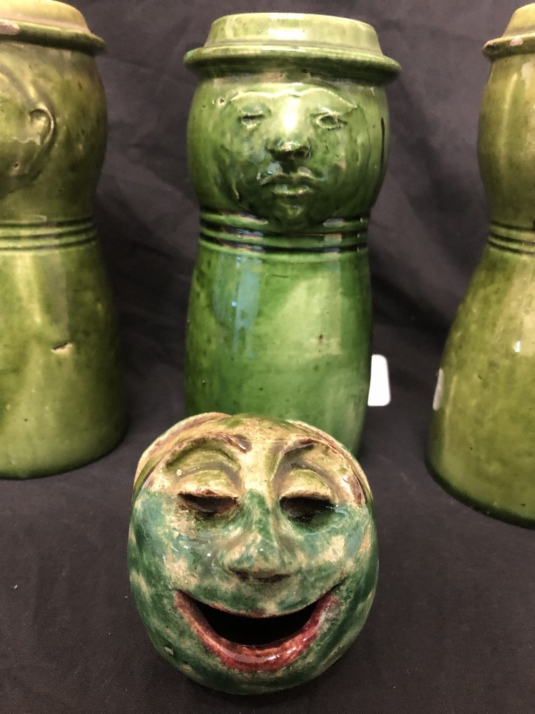 Lot 32 - A collection of four pieces of Farnham Pottery - three jugs and an ornament in the form of people.