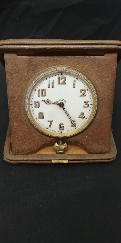 Lot 47 - An eight-day travelling clock in tooled leather.