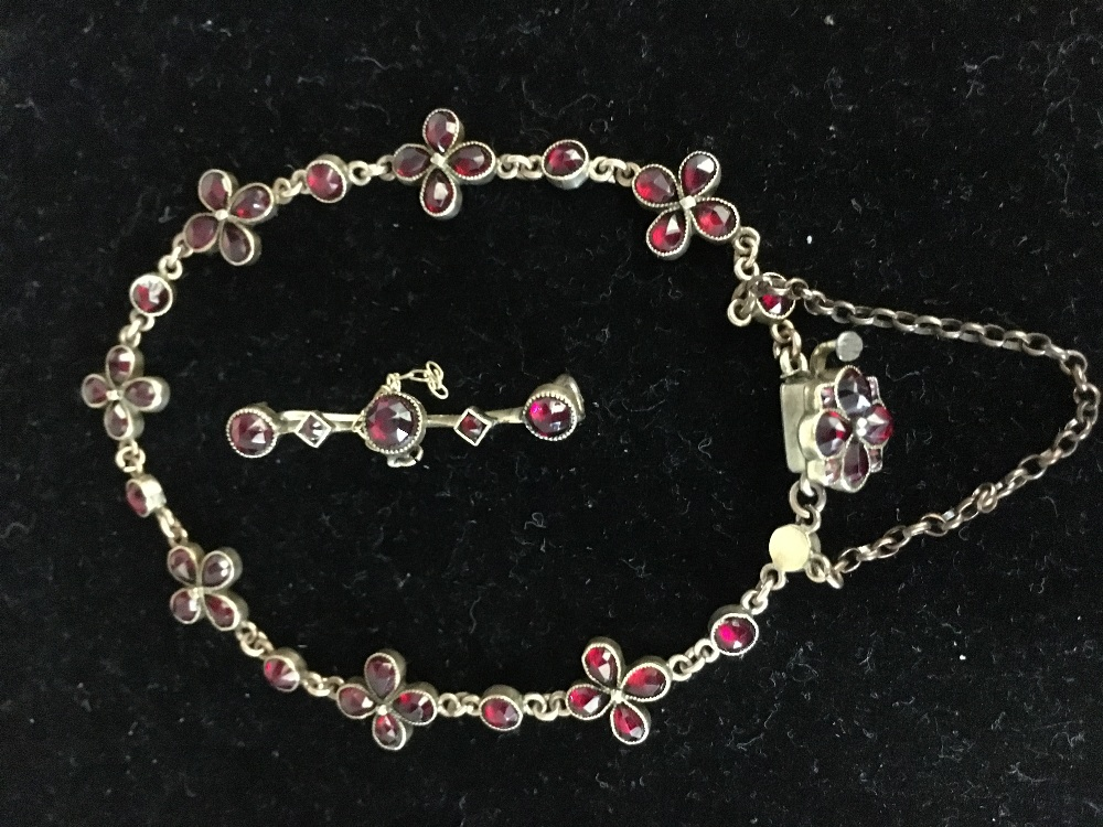 Lot 56 - A yellow metal bracelet set with garnets together with matching bar brooch.