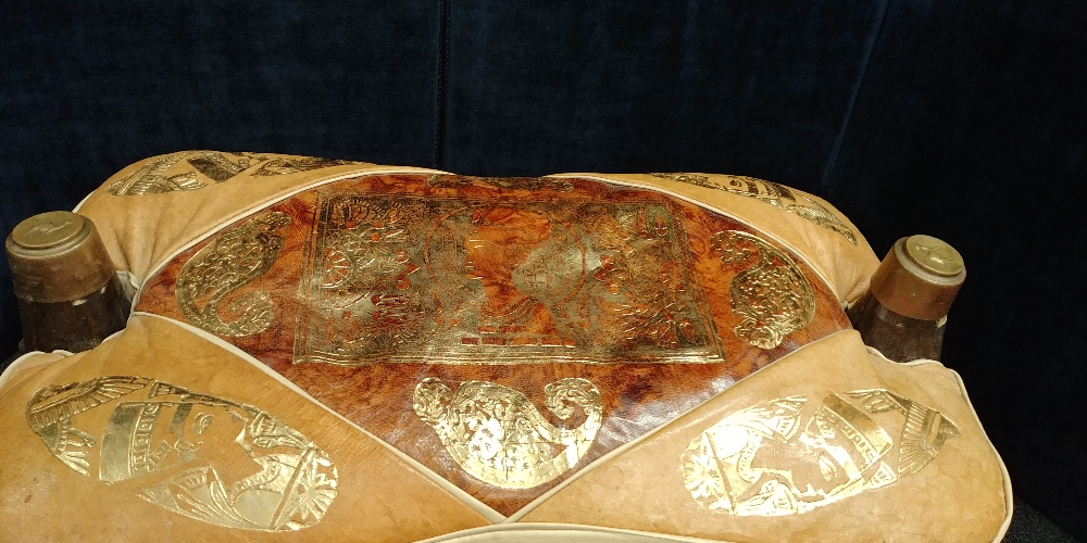 Lot 41 - A camel stool with leather cushion decorated with Egyptian heads and art work.