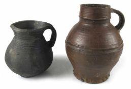Zwei frühe Steinzeug-KrügeNorddeutsch, wohl 14. Jh.H. 17,5/24 cmBauernkeramik. Grauer Scherben mit