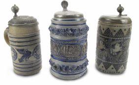 Drei Steinzeug-WalzenkrügeWesterwald, 18./19. Jh.H. 21/25,5 cmGrauer Scherben, Salzglasur, blaue