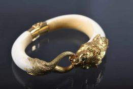 ArmreifBein und Metall vergoldet, vollplastisch gearbeitet, in Form eines Löwenkopfes, seinen