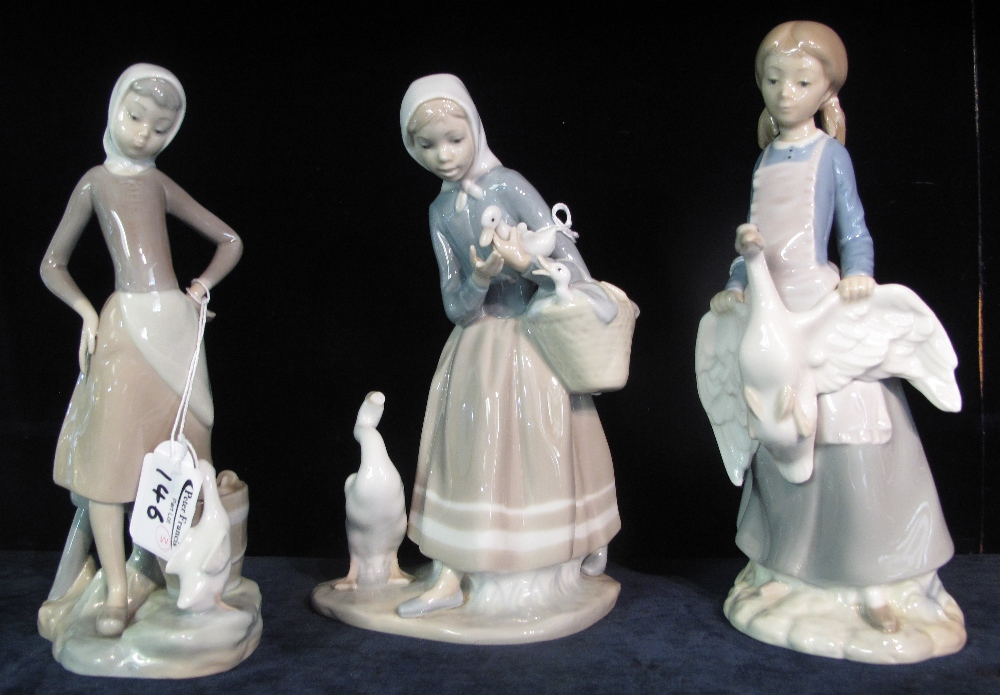 Lot 146 - Two Lladro Spanish porcelain figurines together with a Nao Spanish porcelain figurine of a girl