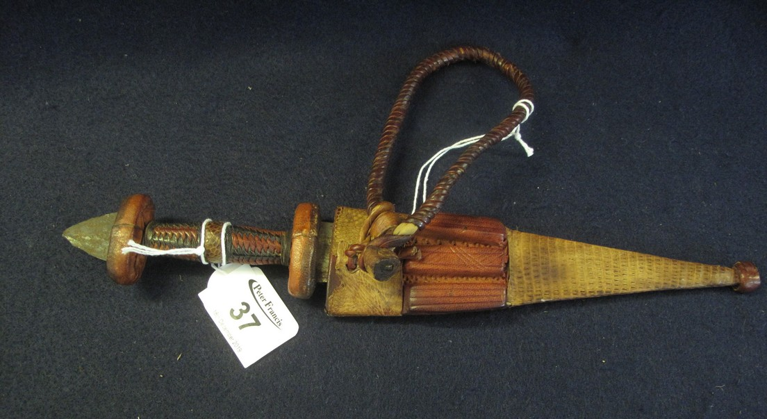 Lot 37 - Small African dagger with leather hilt having reverse blade and snakeskin covered scabbard. (B.P.