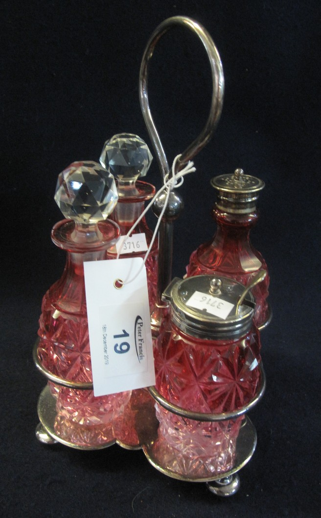 Lot 19 - Silver plated and cranberry glass four section cruet set on stand. (B.P. 24% incl.