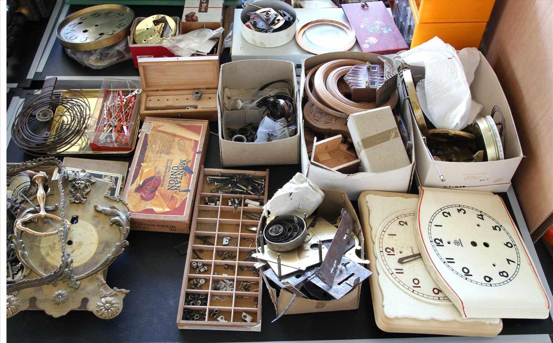 Los 33 - Konvolut UhrenteileAuf und unter sechs Tischen (Tische nicht im Auktionsumfang enthalten). Werke,