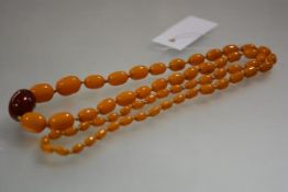 A long single strand butterscotch and cherry amber necklace, early 20th century, the central largest