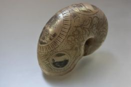 A 19th century engraved nautilus shell, decorated with cartouches of a house sheltered by a tree,