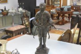 A knight in armour fireside companion set, early 20th century, the standing figure holding a sword-