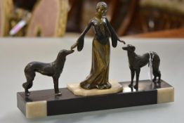 A 1920's patinated metal group of a lady flanked by a pair of borzoi dogs, on a cream and black