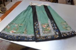 A Chinese silk and silk needlework skirt, c. 1900, worked in colours and metallic threads with