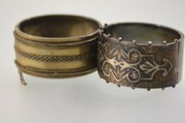 Two 19th century silver cuff bangles, each hinged, the first with applied strapwork and engraved