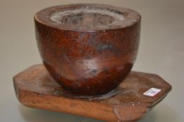 A large 19th century burr elm and elm mortar on stand, the burr mortar with inset rim, raised on a