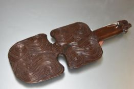 A Maori wooden club, Kotiate, of characteristic form, with incised scrolling decoration, the