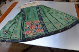 A Chinese silk and silk needlework skirt, c. 1900, worked in colours with flowers and floral bands