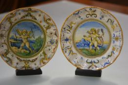 A pair of Cantagalli maiolica plates, c. 1900, of Urbino type, each painted to the well with a putto