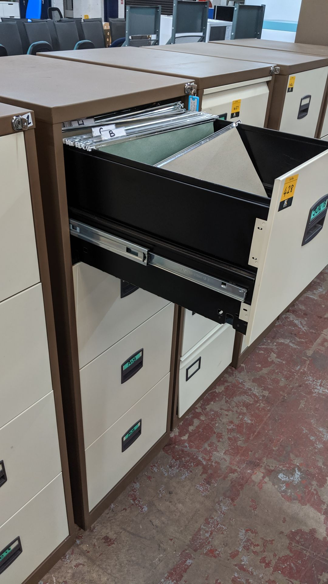 Lot 428 - Brown metal 4-drawer filing cabinet with key. This is one of a large number of lots used/owned by