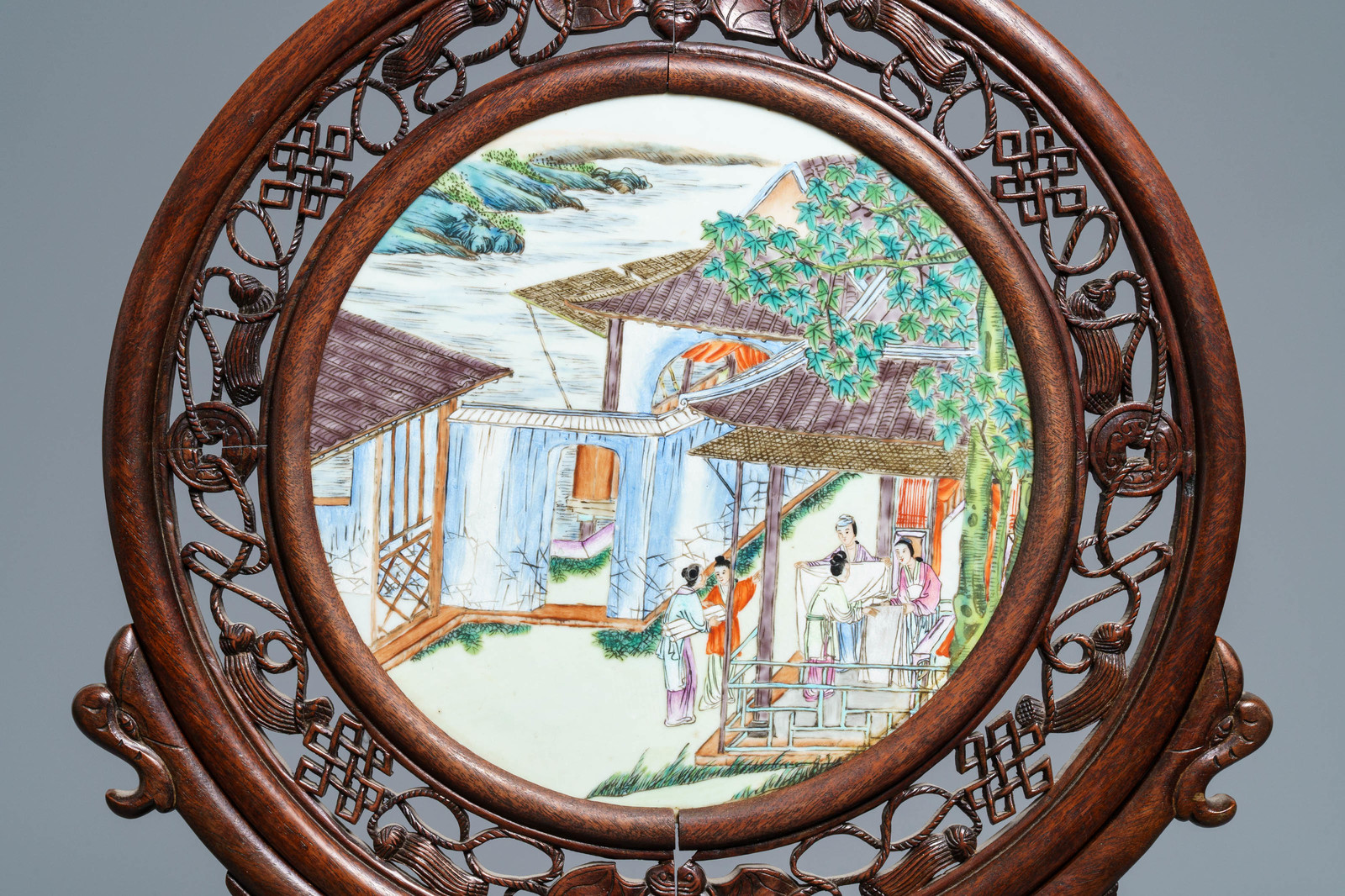 Lot 17 - A Chinese carved wooden screen with a famille rose plaque, 19/20th C.