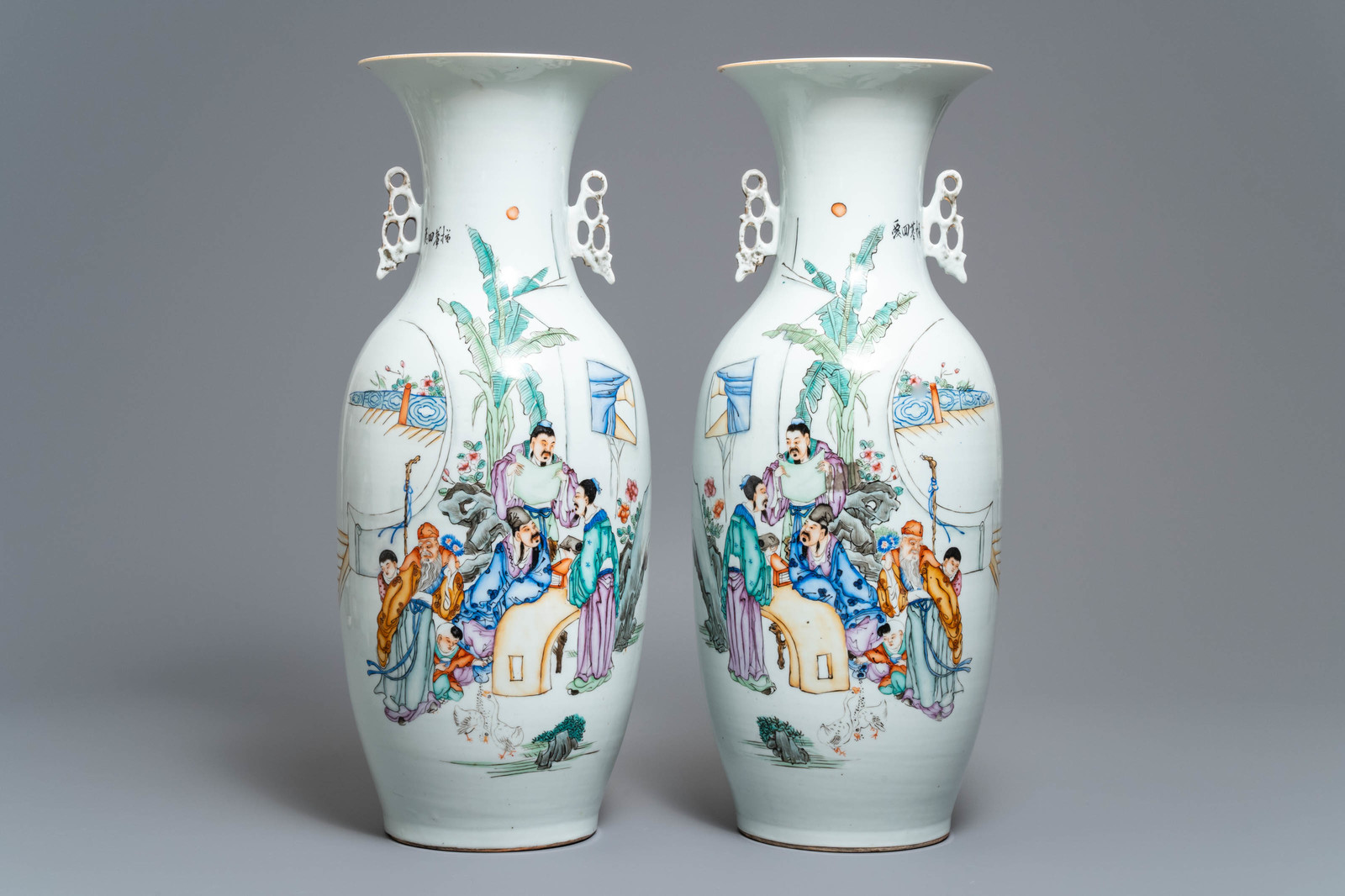 Lot 33 - A pair of Chinese famille rose vases with scholars in a garden, 19/20th C.
