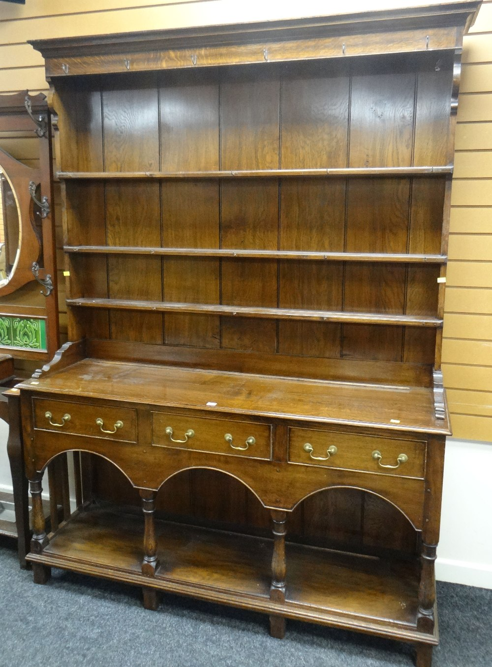 Lot 25 - 20TH CENTURY OAK WELSH DRESSER having an open base with arched frieze, three drawers and open