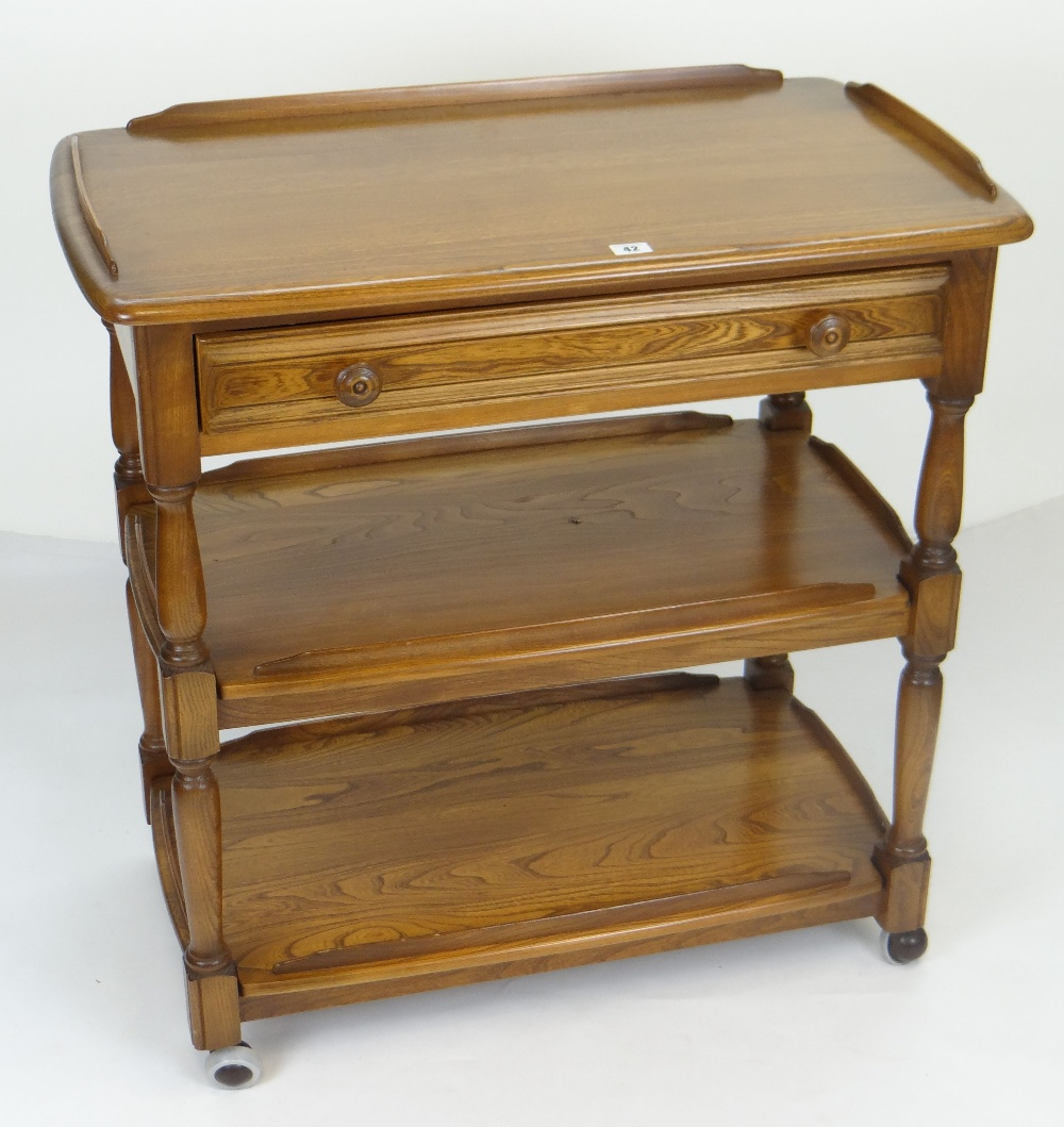 Lot 42 - ERCOL THREE TIER TEA TROLLEY on casters, cutlery drawer and gallery top, 78cms wide