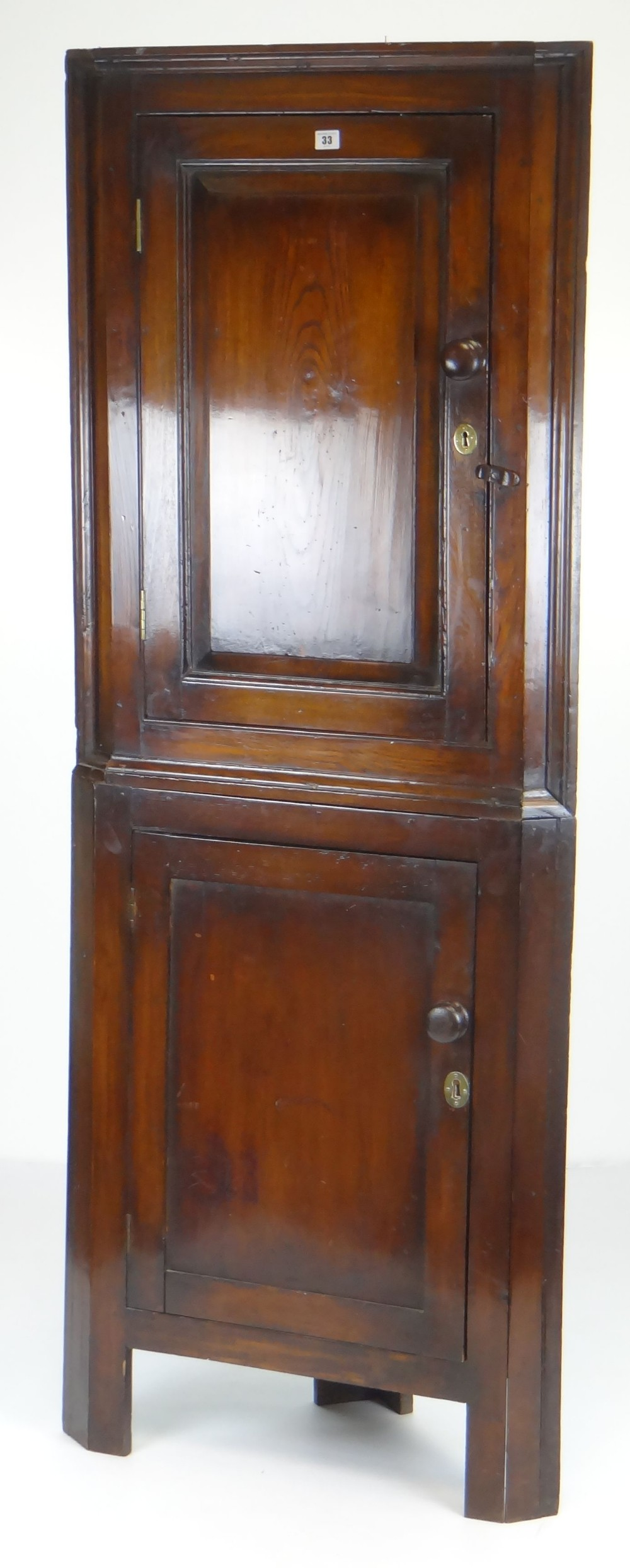 Lot 33 - ANTIQUE STANDING TWO STAGE CORNER BLIND-CUPBOARD the top section with panelled door in elm, turned