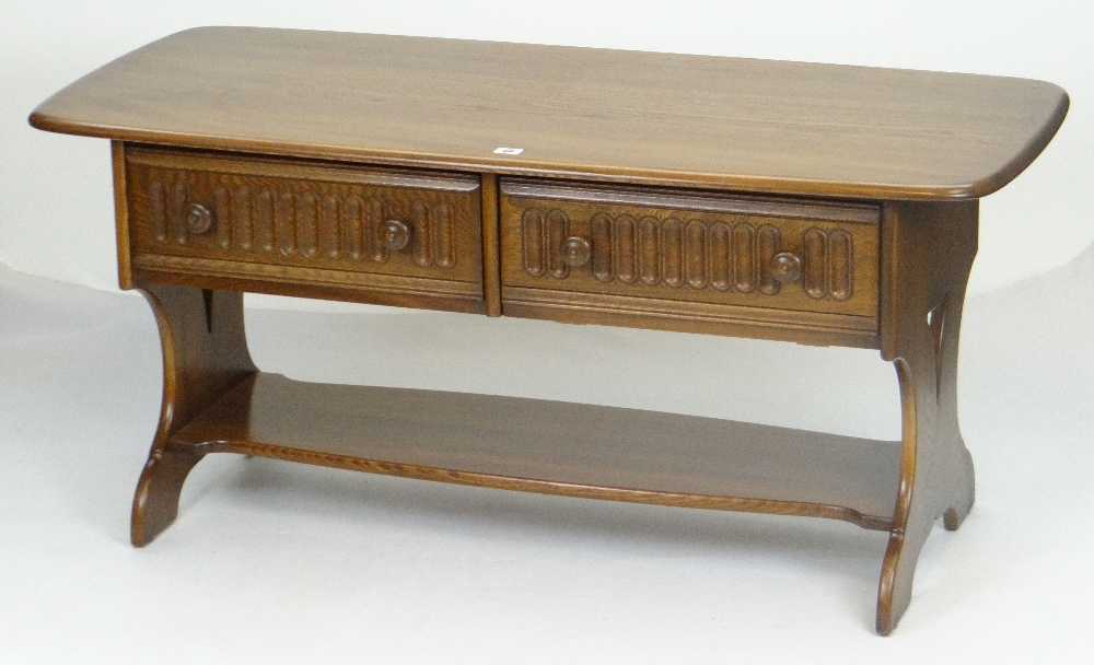 Lot 38 - ERCOL LONG JOHN COFFEE TABLE of rounded rectangular form, two fluted drawers with turned knobs and