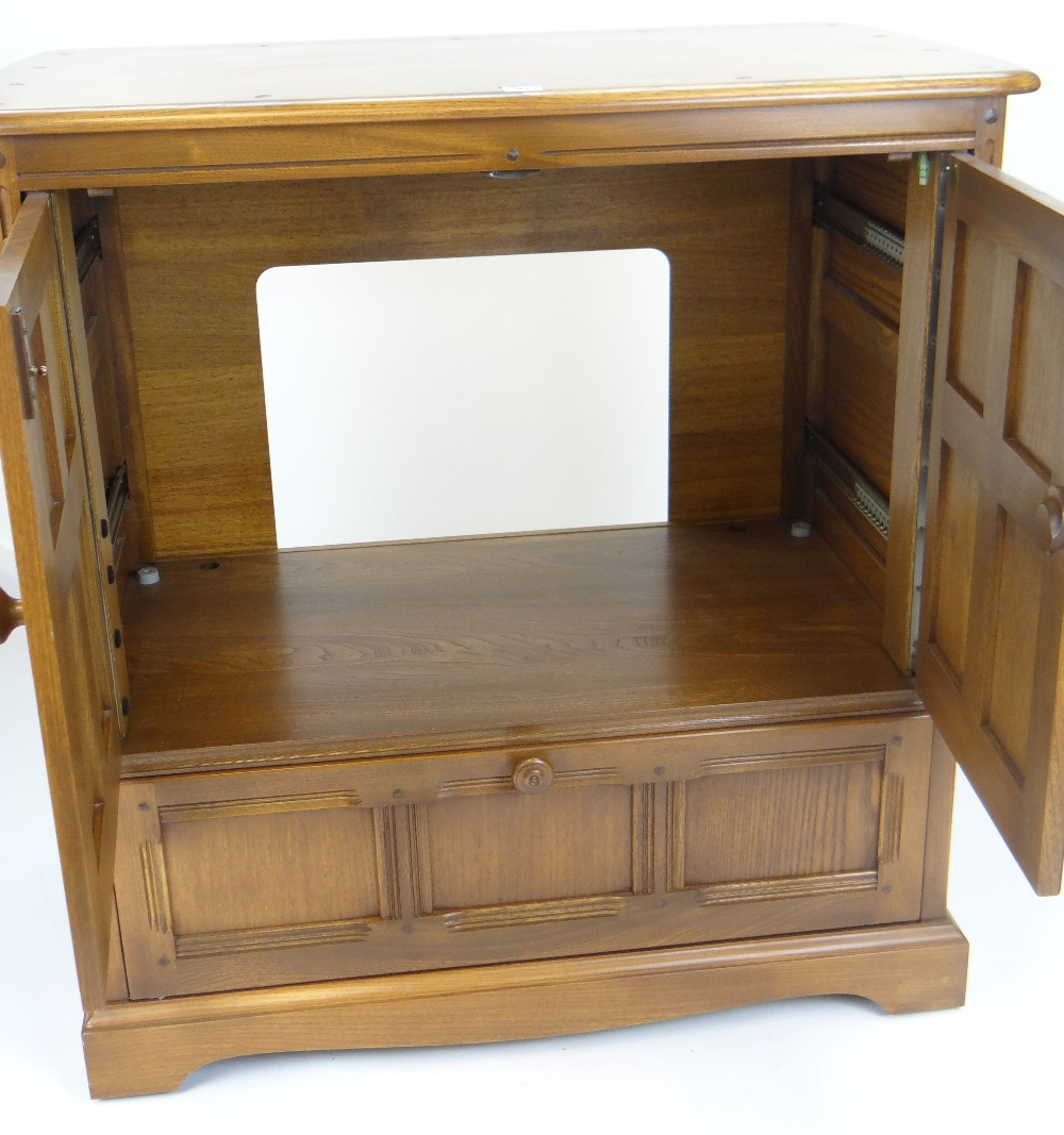 Lot 41 - ERCOL TV CABINET with base drawer and carved panel design, 92cms wide