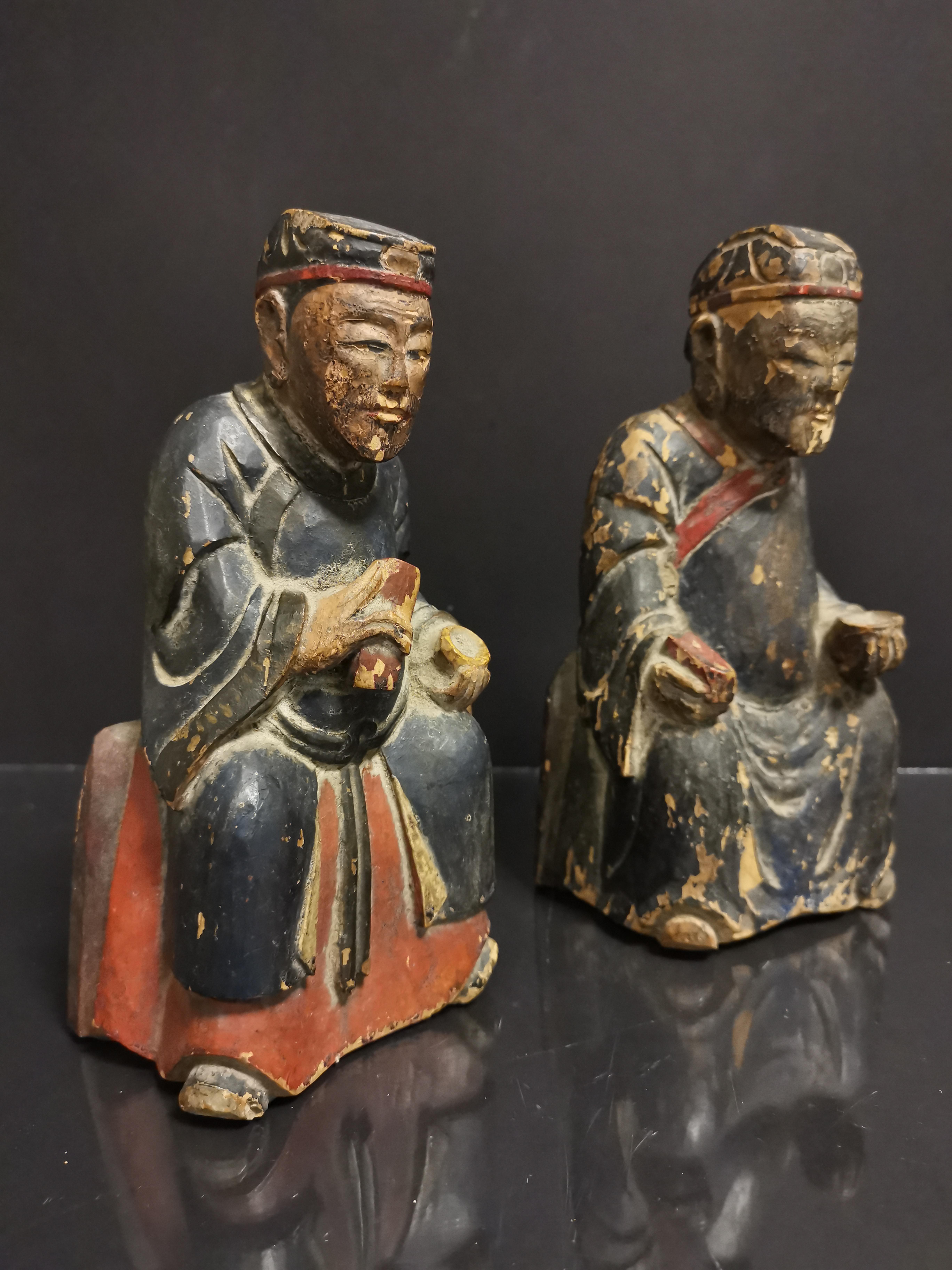 Lot 28 - CHINE. Deux lettrés assis tenant un bol et une tablette, bois sculpté. H : 19 cm. -