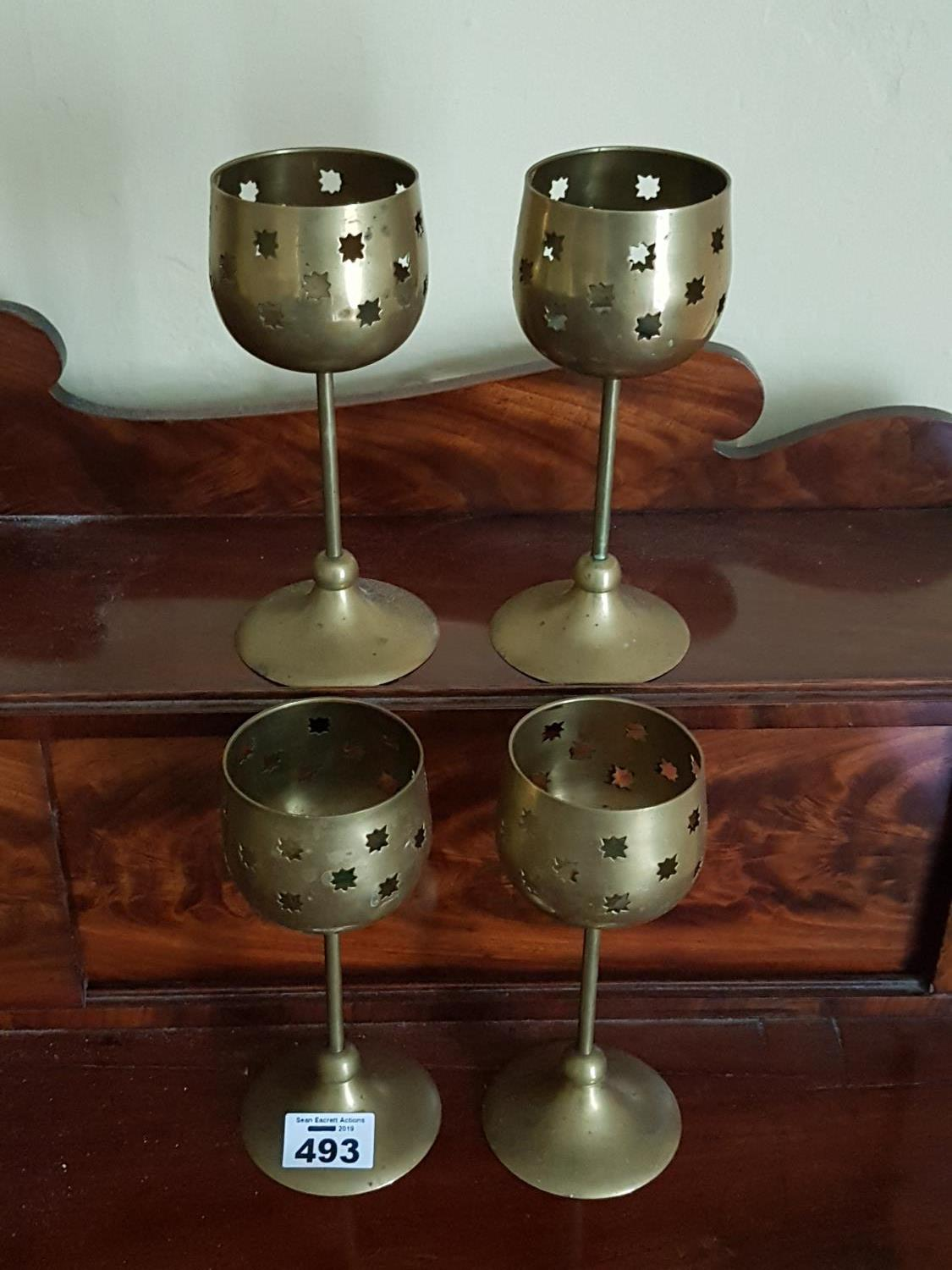 Lot 493 - A set of four Brass Candle Holders.