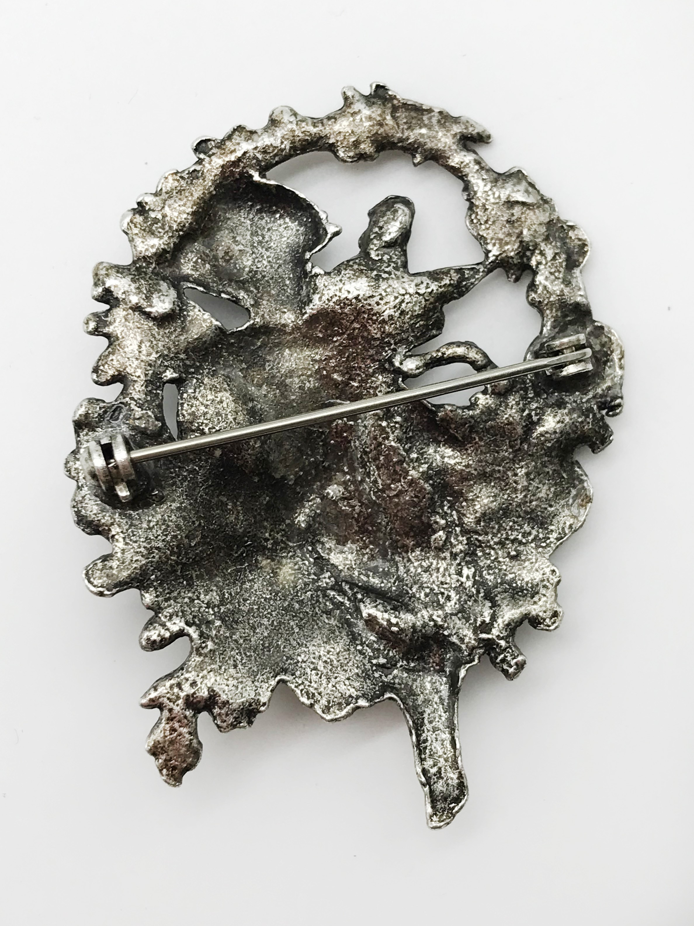 Lot 21 - WHITE METAL ORNATE LARGE BROOCH WITH CHERUB