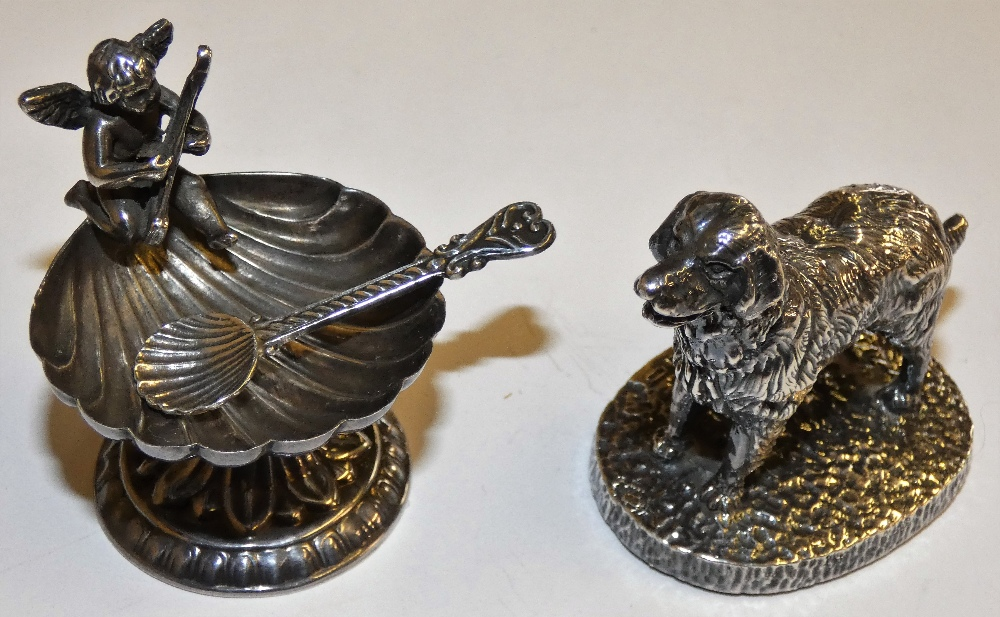 Lot 134 - A sterling silver model of a cherub upon a steel spoon together with a silver model of a dog,