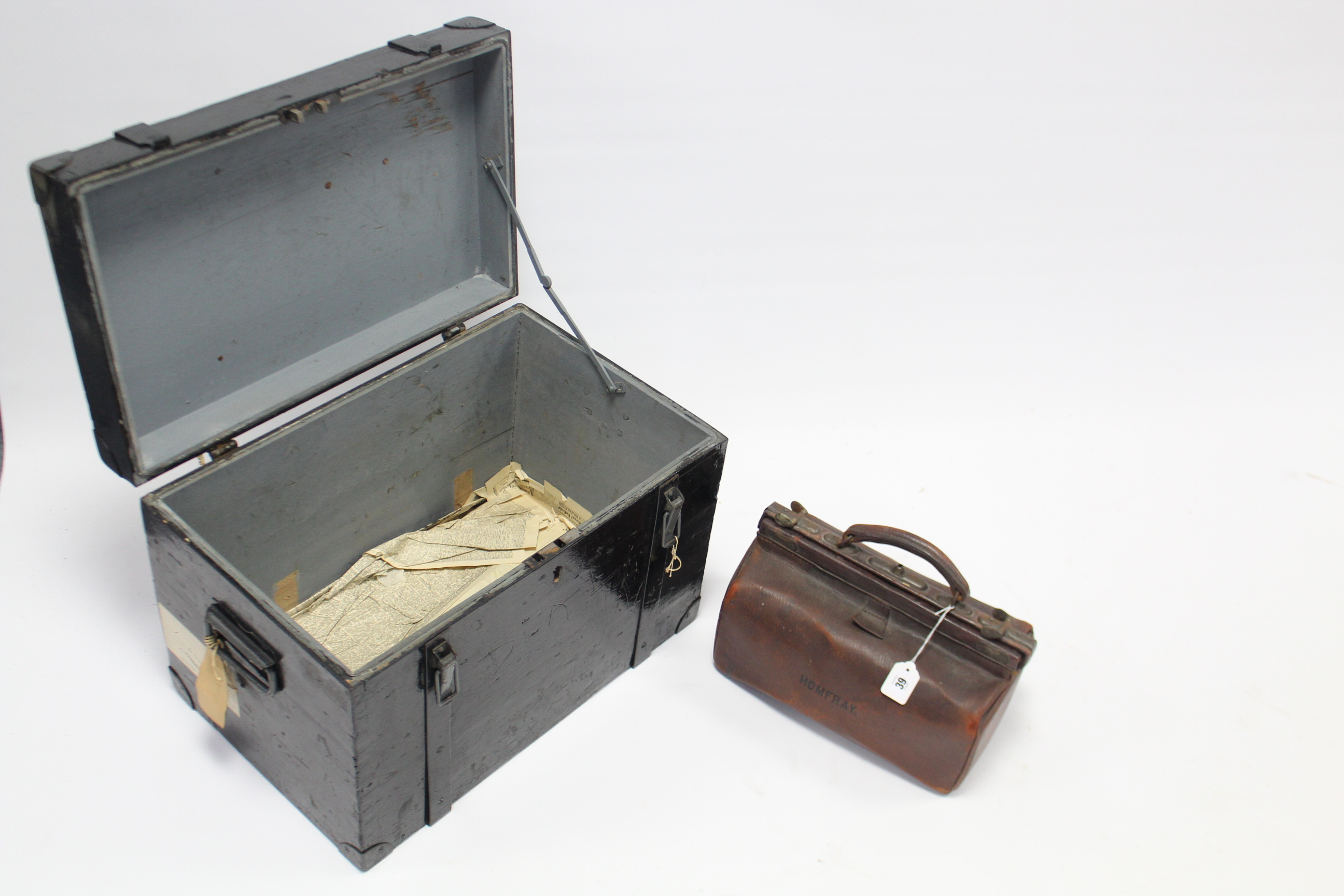 """Lot 39 - An early 20th century Gladstone-type leather bag, 14"""" wide; & a black painted iron-bound deal strong"""