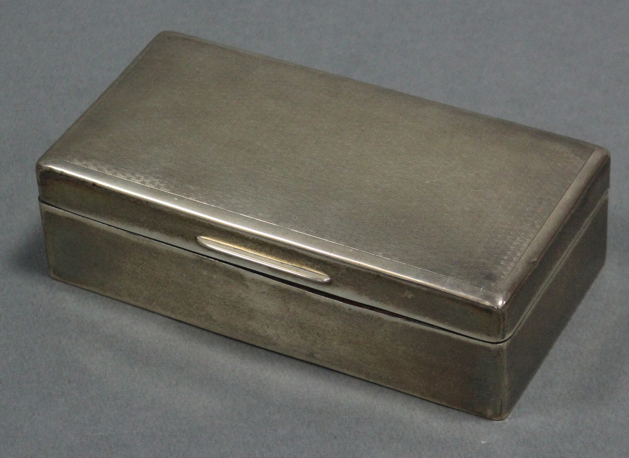 "Lot 12 - An engine-turned cigarette box with hinged lid, 7"" x 3½""; London 1923, by A M & M Ltd."