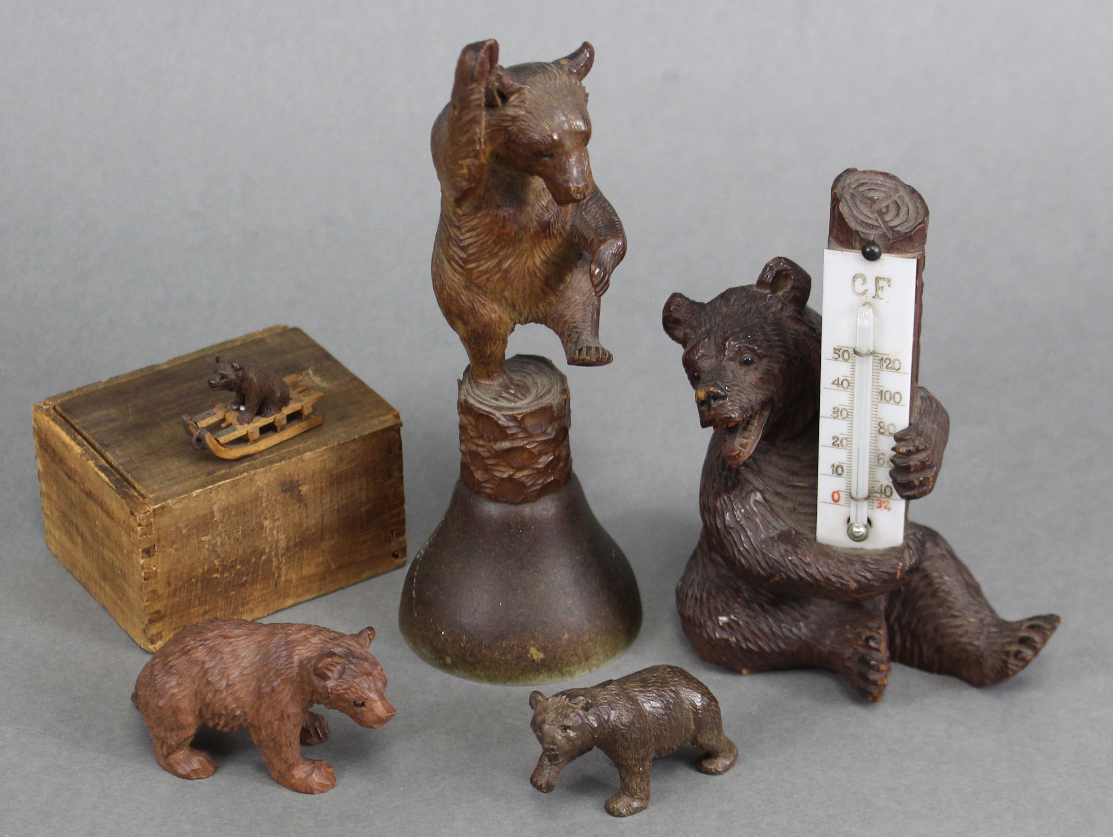 "Lot 198 - A Black Forest carved wood seated bear holding a thermometer, 5"" high; a ditto table bell, the"