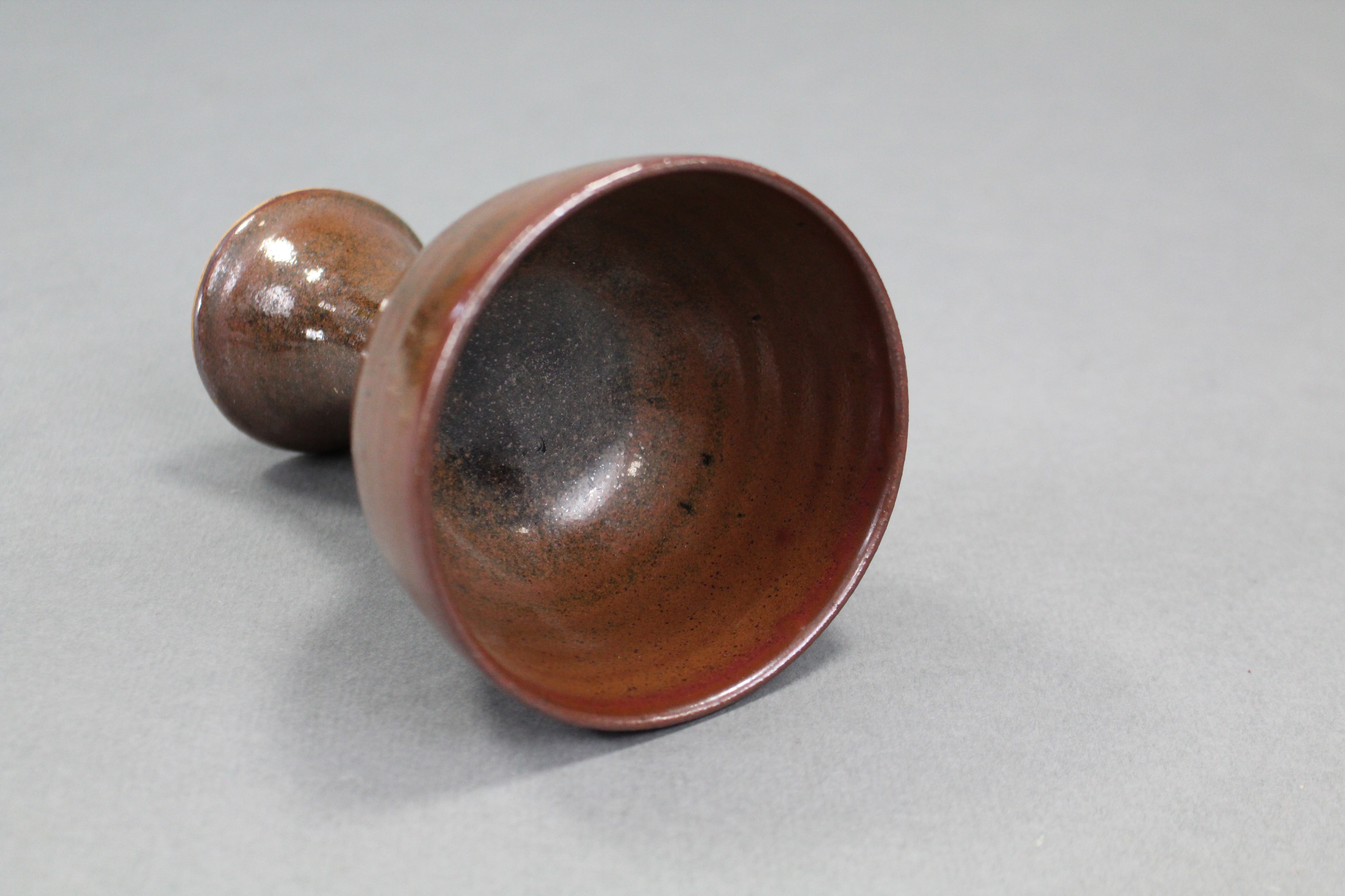 """Lot 390 - A Chinese brown-glazed stoneware stem cup; 4"""" diam. x 5½"""" high."""