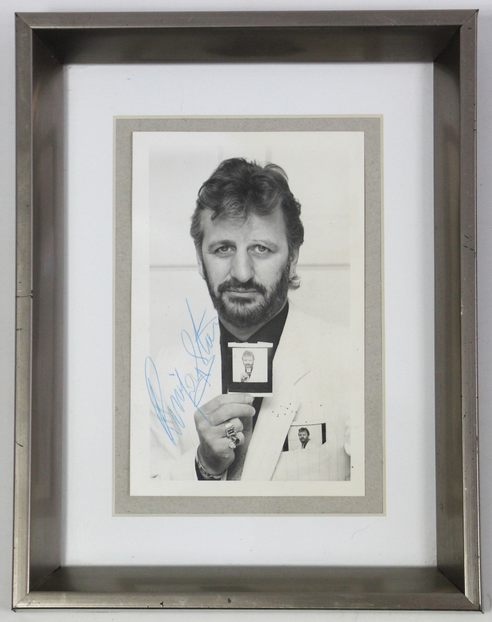 "Lot 35 - AN AUTOGRAPHED PHOTOGRAPH of RINGO STARR, 5½"" x 3¼"", in glazed frame."
