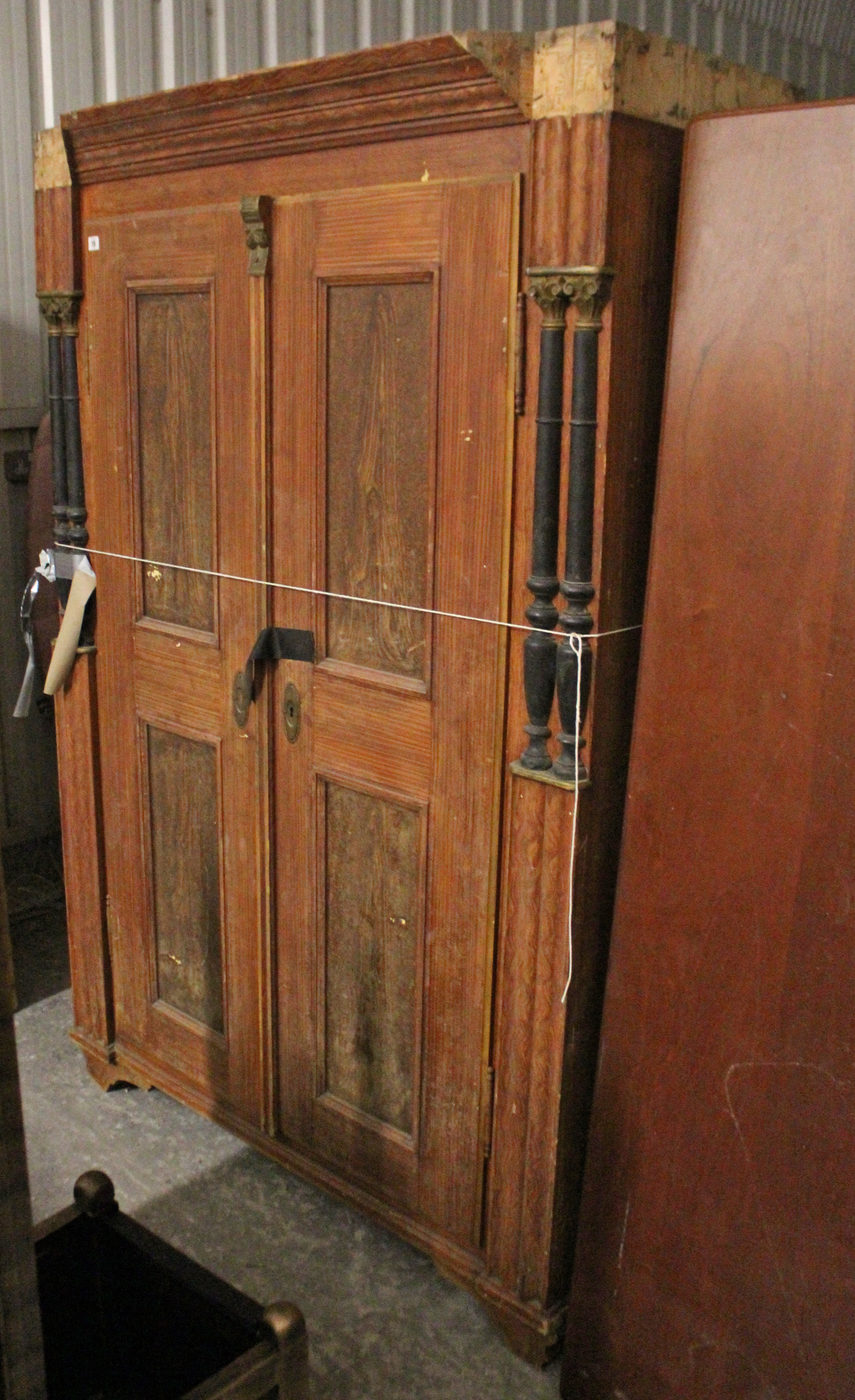 Lot 15 - A continental-style grained pine wardrobe enclosed by pair of panel doors, with half turned