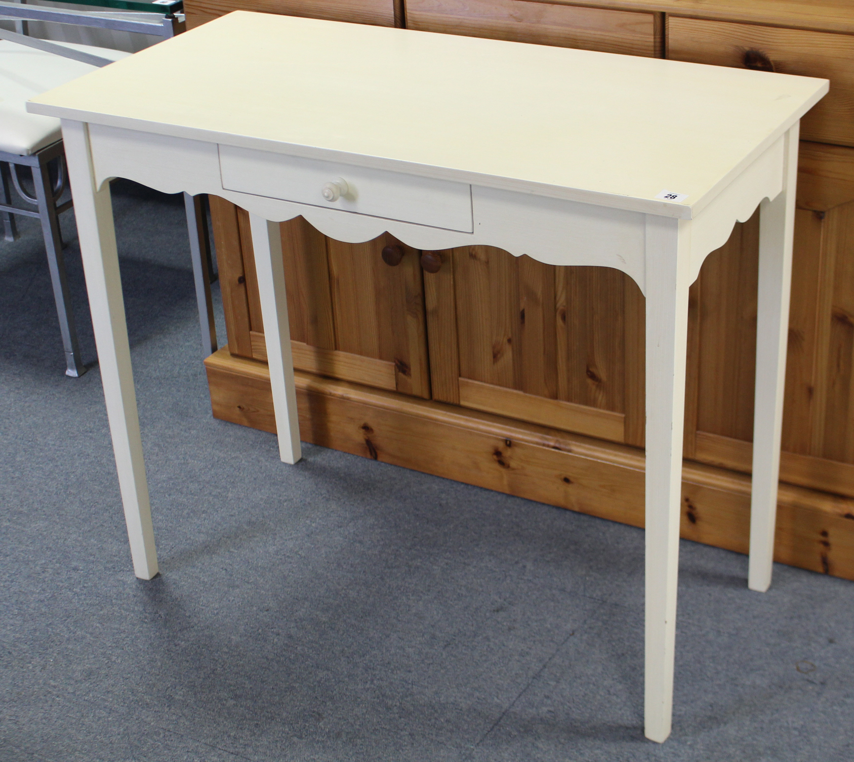"""Lot 28 - A white-finish side table fitted centre frieze drawer, & on square tapered legs, 36"""" wide."""