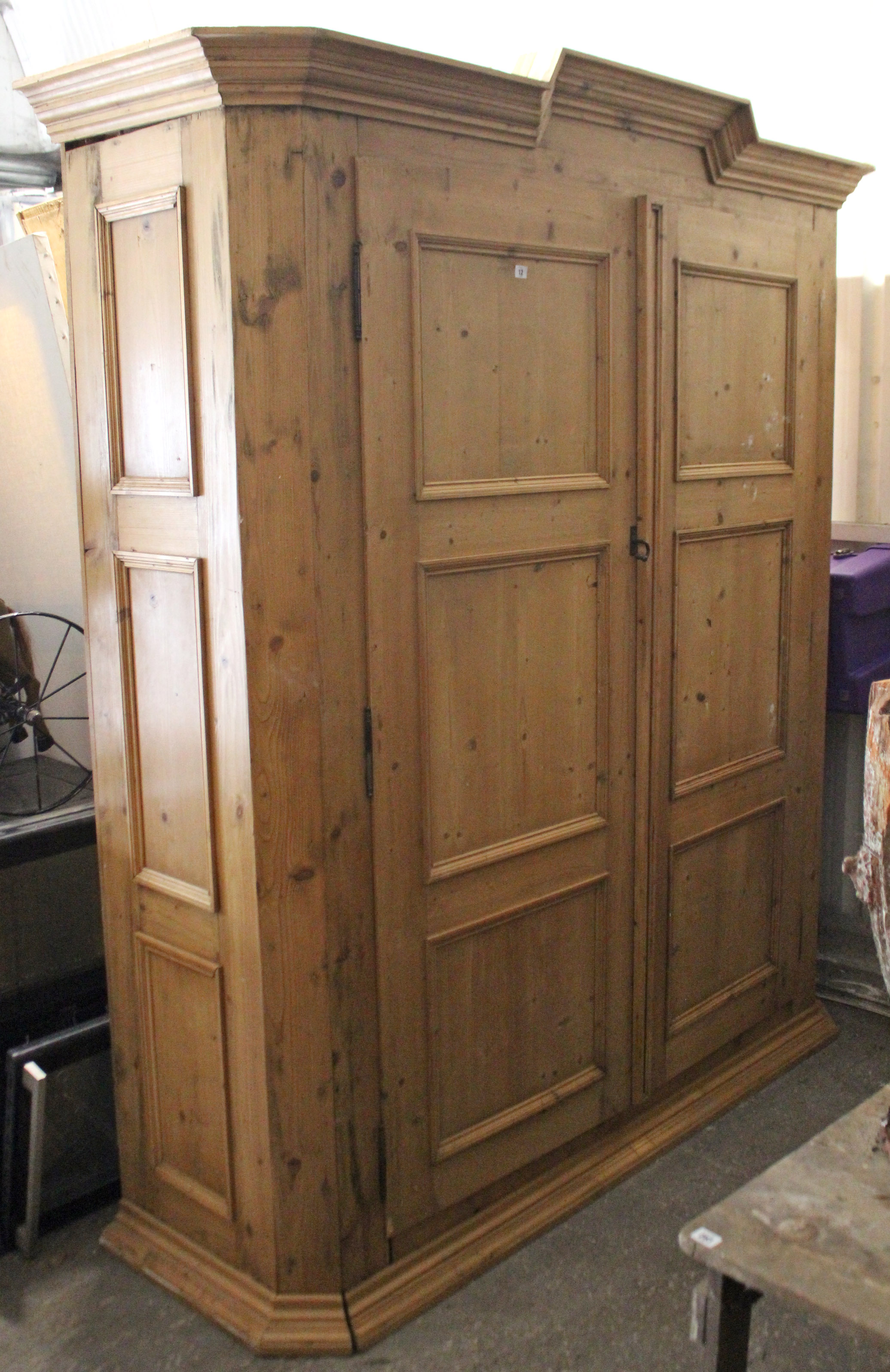 Lot 12 - A continental-style large pine wardrobe with moulded cornice, enclosed by pair of panel doors, &