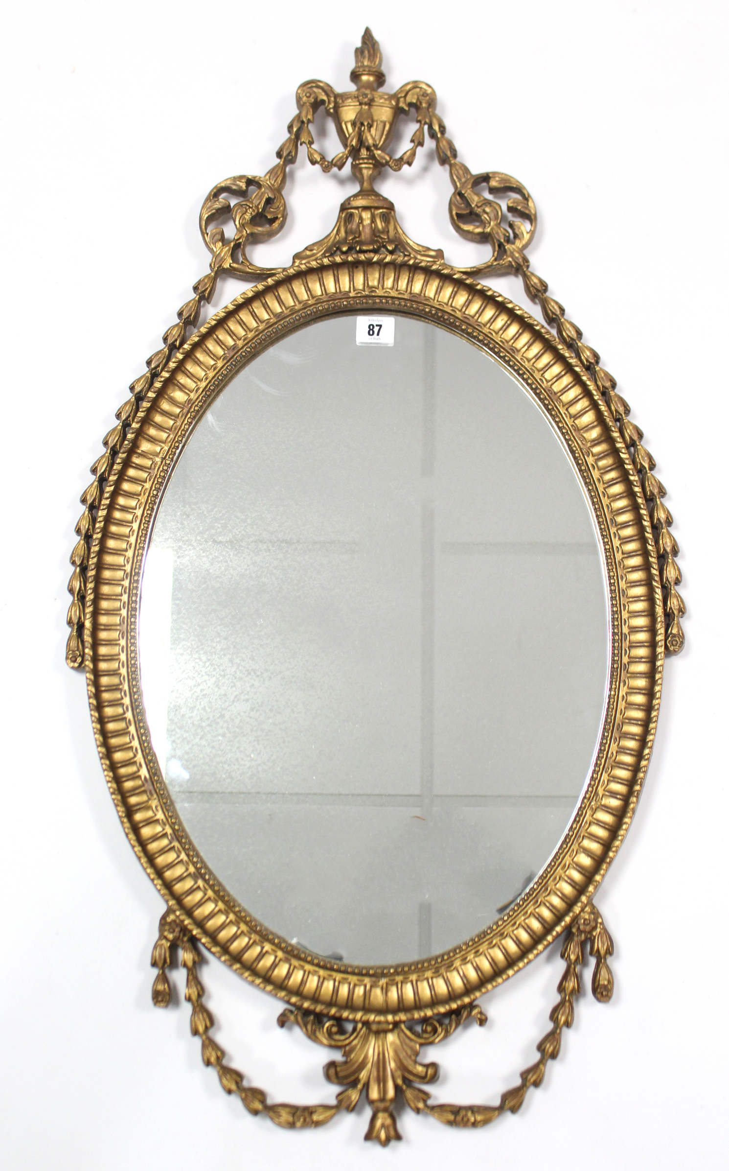 "Lot 87 - A reproduction gilt frame oval wall mirror in the Adam style, 36"" x 19""."