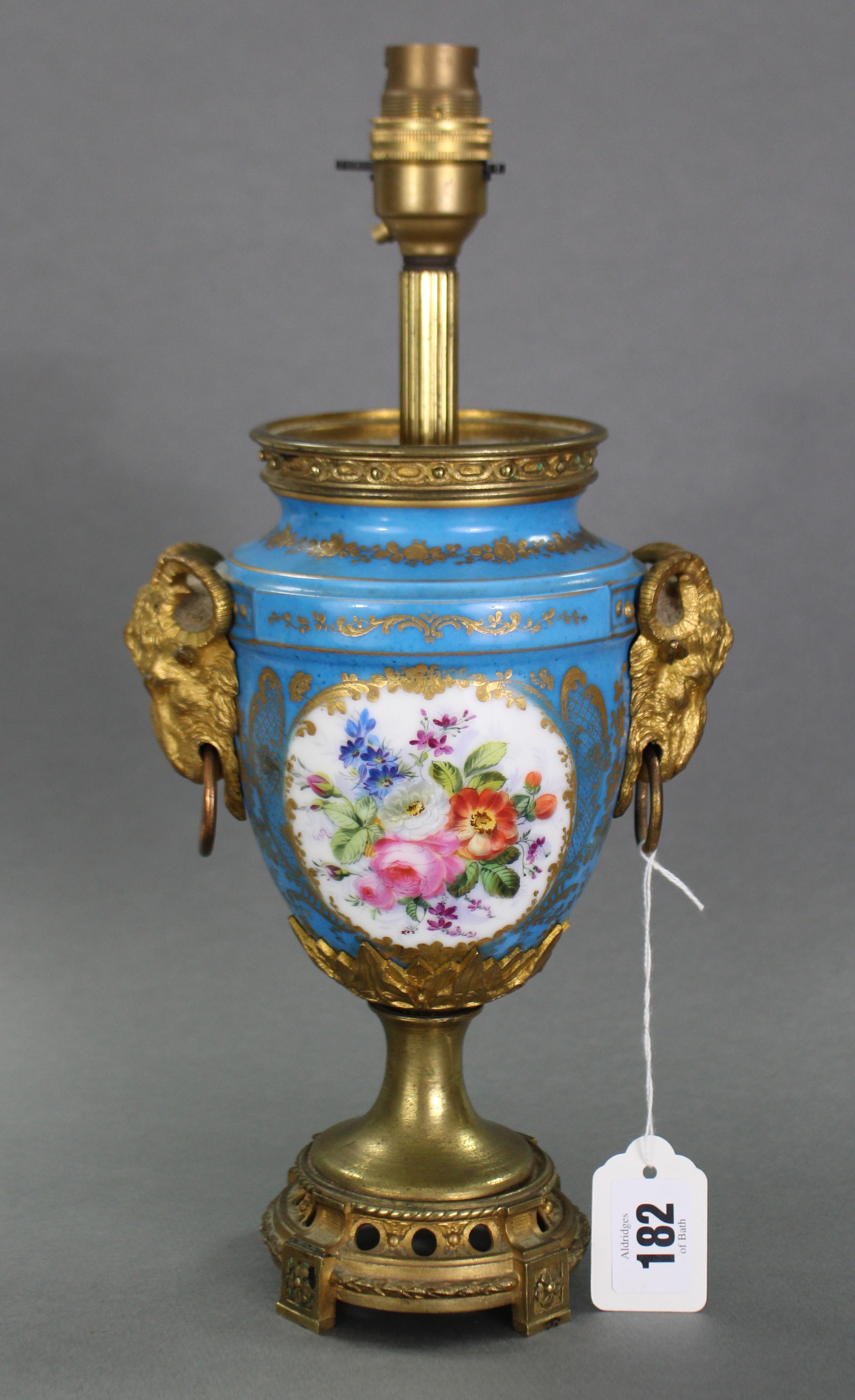 Lot 182 - A continental porcelain & gilt Ormolu ovoid table lamp with two hand painted panels with rams-head
