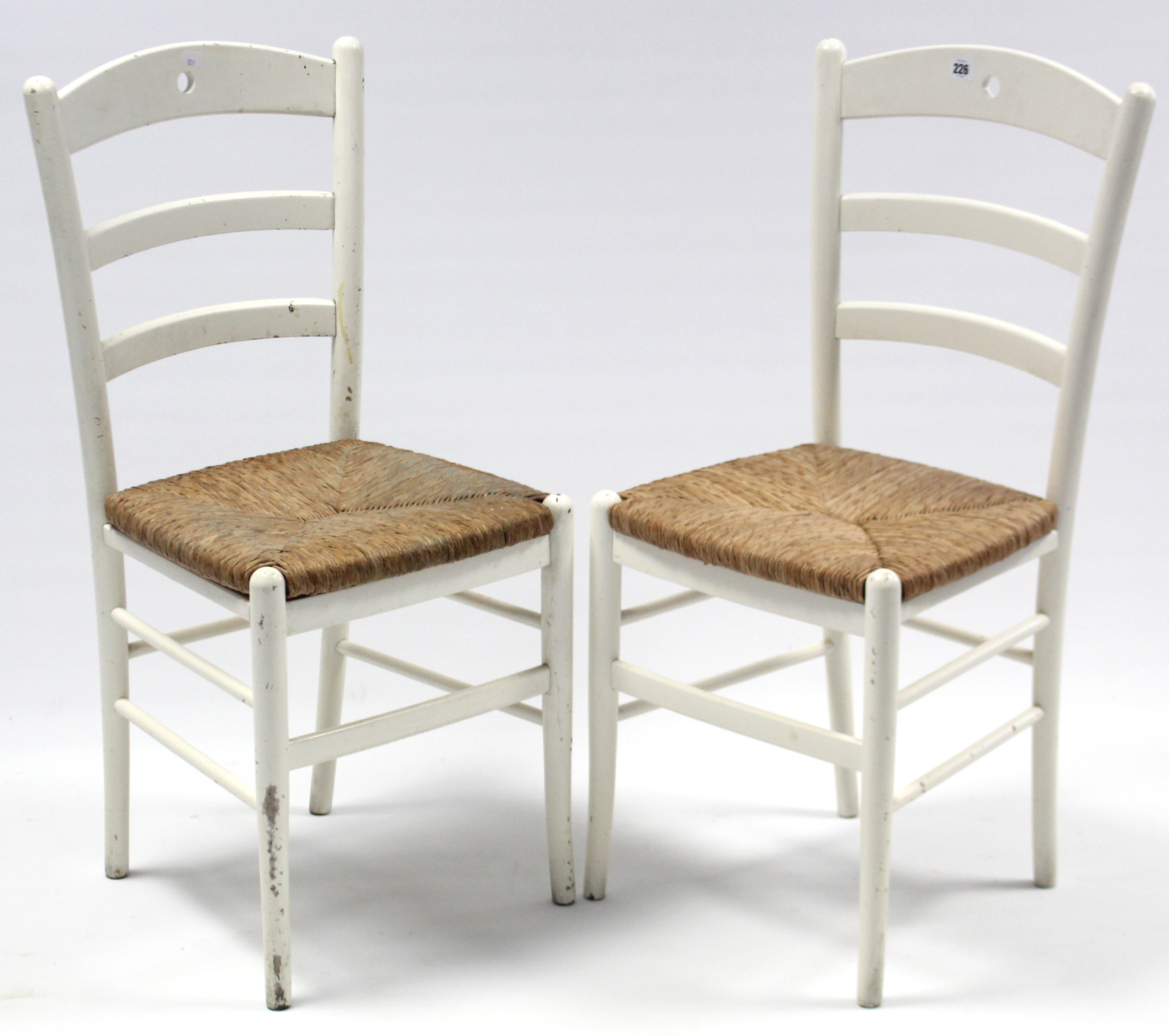 Lot 261 - A pair of white painted wooden ladder-back kitchen chairs with woven rush seats, & on round