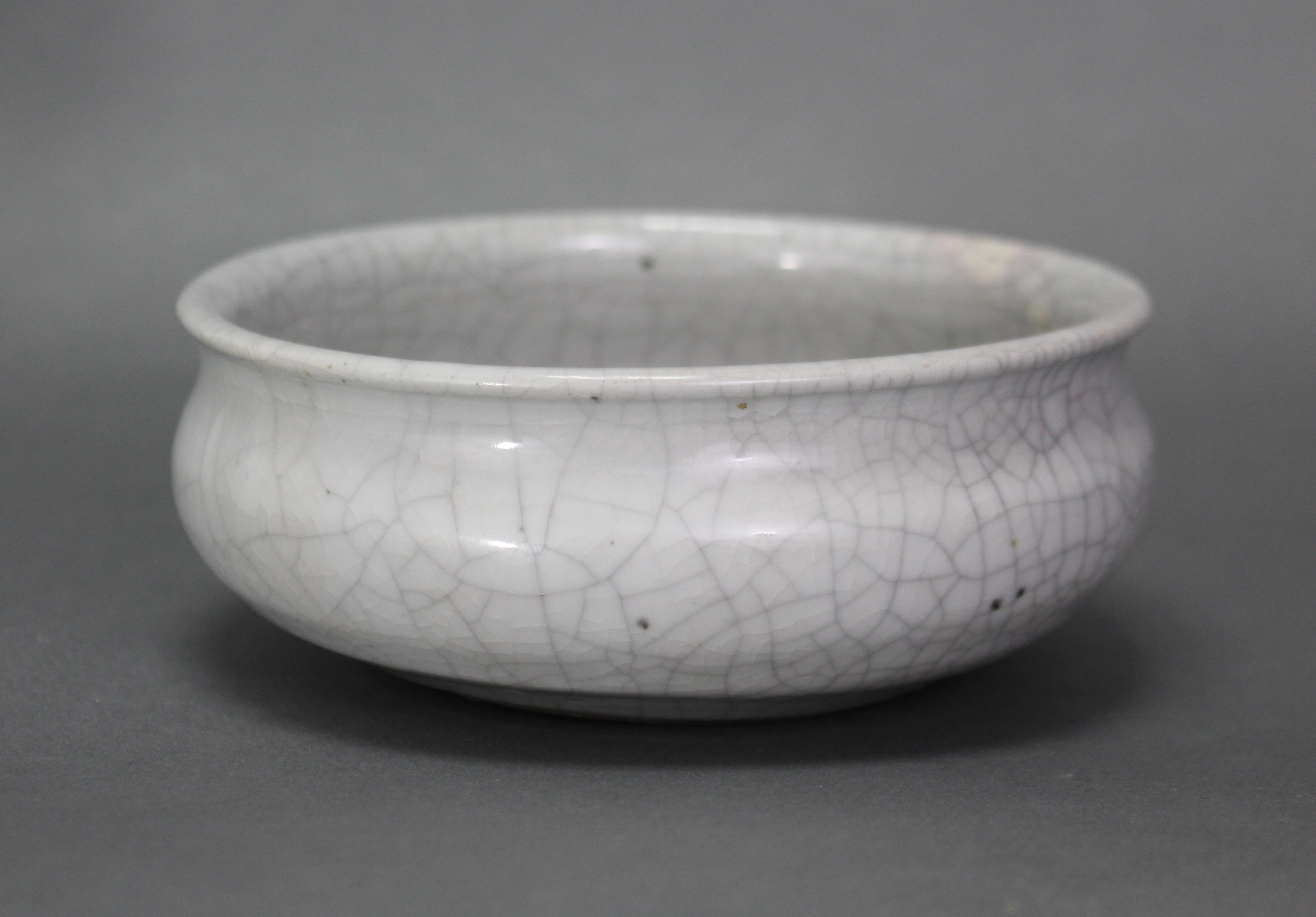 Lot 214 - A Chinese Guan-type brush washer of squat round form with slightly flared rim, pale grey crackle