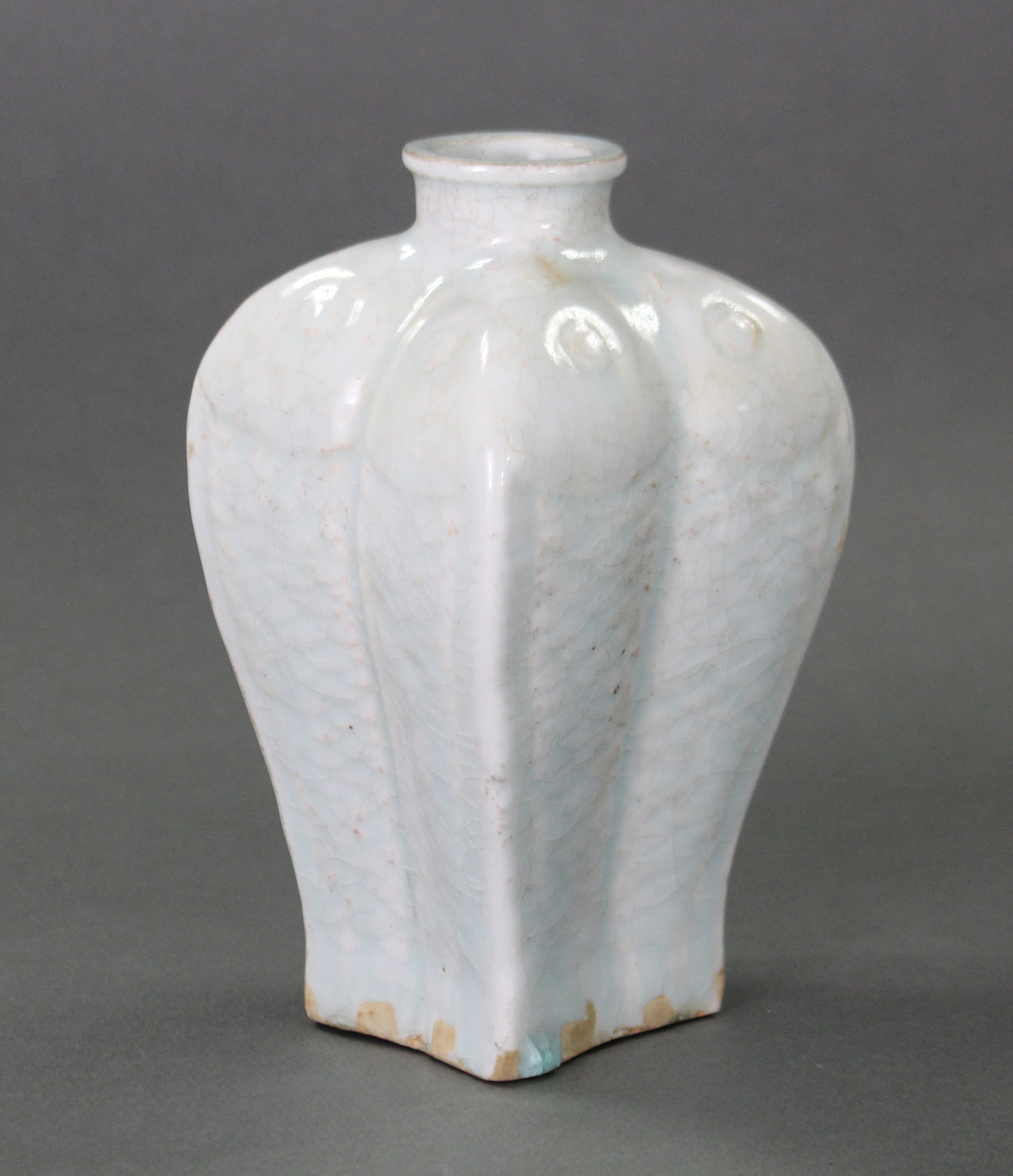 Lot 216 - An unusual oriental porcelain baluster vase moulded in low relief as four conjoined fish, with short
