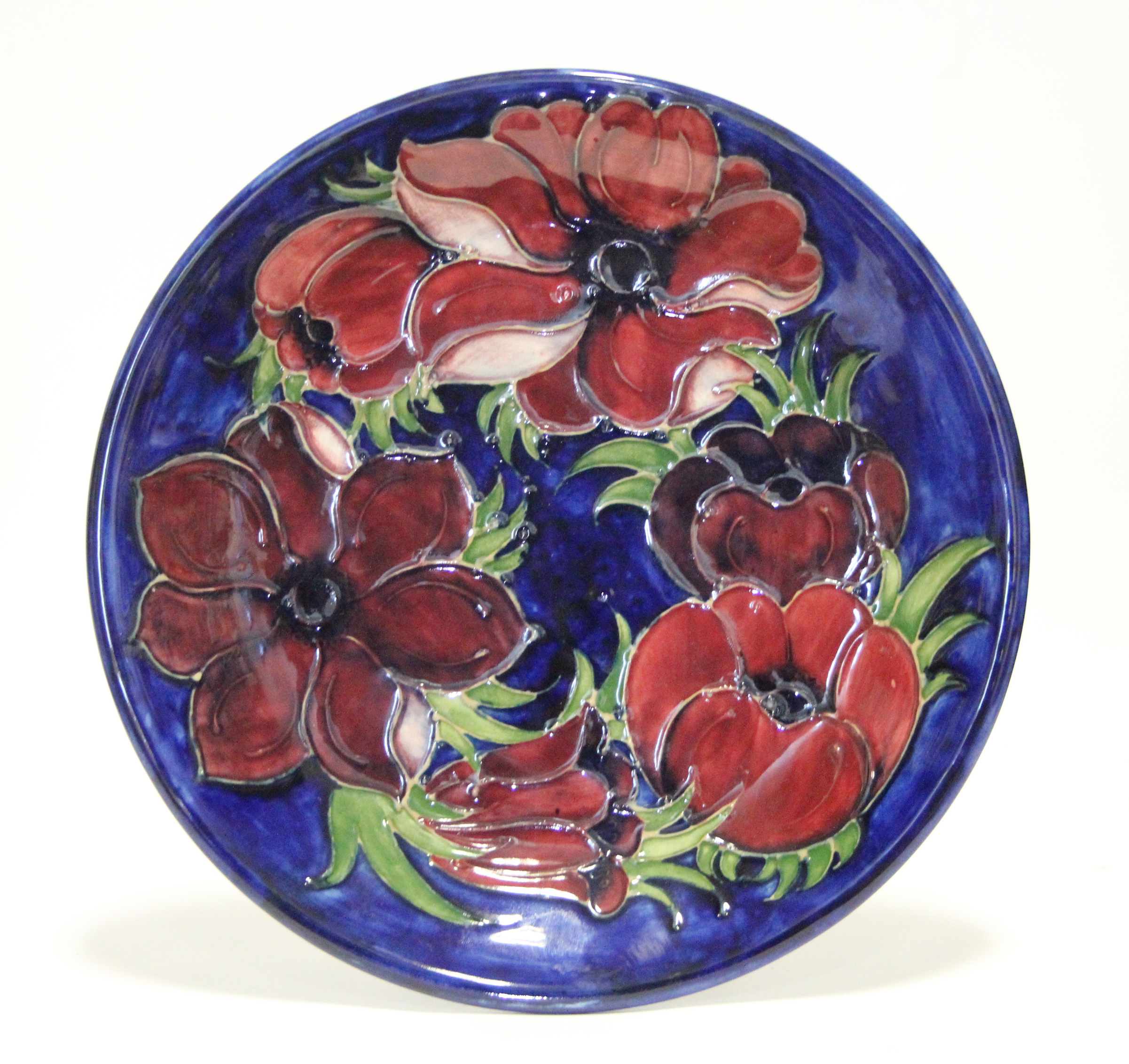 """Lot 167 - A Moorcroft """"Anemone"""" plate of deep blue ground, painted initials & impressed marks; 10"""" diam."""