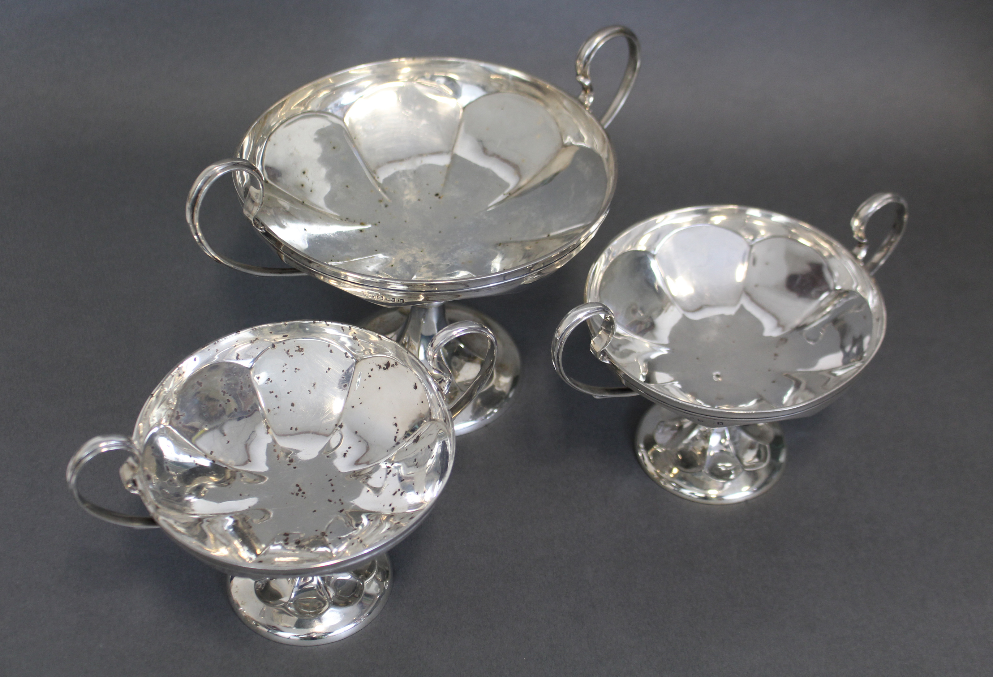 Lot 40 - A suite of three Edwardian silver comports of tazza form, each with loop side handles to the shallow